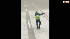 Il guide l'avion en se déhanchant sur le tarmac